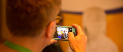 A man is looking at the view screen of a digital camera. On the screen is a black man standing