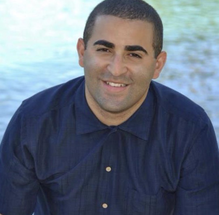 Dominican male wearing a blue buttoned down collared shirt. The image zoomed in to his head and shoulders. He sits in front of a body of water, smiles directly at the camera.