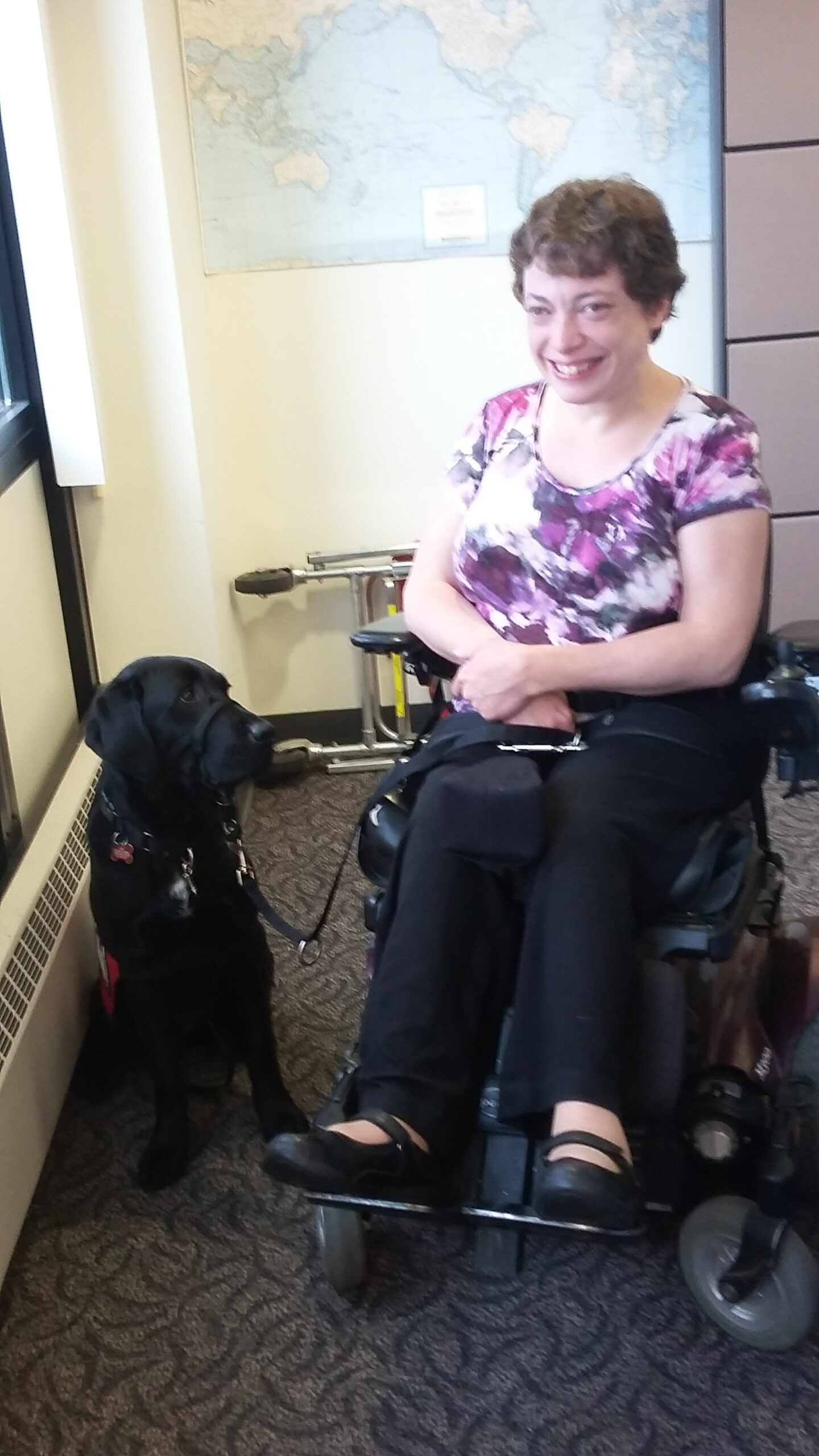 Tracy is smiling next to her mobility assist dog, Gidget.